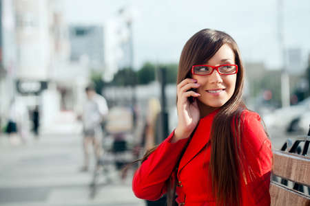 llamando: sonriendo empresaria llamando por tel�fono, que llevaba gafas de color rojo