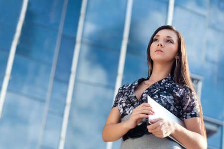 laptop outside: beautiful woman holding laptop over glass building background
