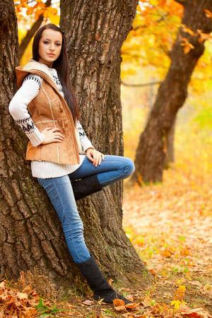 autmn: brunette woman near tree in autmn park