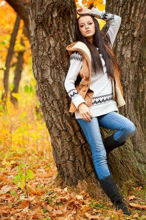 autmn: brunette woman fashion model near tree in autmn park