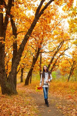 autmn: brunette woman walking in autmn park