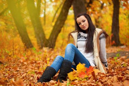 autmn: brunette woman sitting on fallen leaves in autmn park