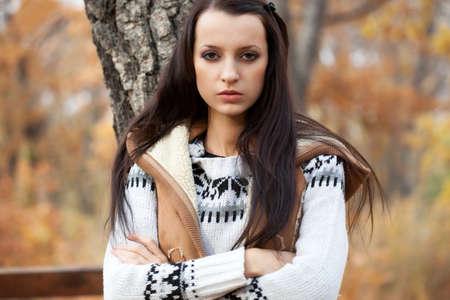 autmn: brunette woman looking at camera near tree in autmn park Stock Photo