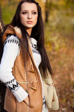 autmn: brunette woman standing near tree in autmn park Stock Photo