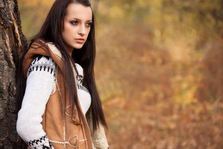 autmn: young adult brunette woman standing near tree in autmn park