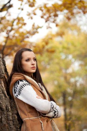 autmn: brunette woman posing near tree in autmn park, copy space