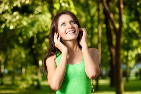 happy woman listening the music in summer park photo