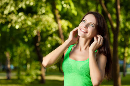 happy brunette listening music  in summer park photo