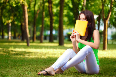 brunette woman cover the face with book at park summer park photo