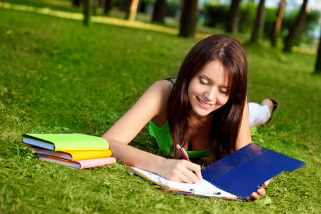 writing book: woman laying on grass and writing in park