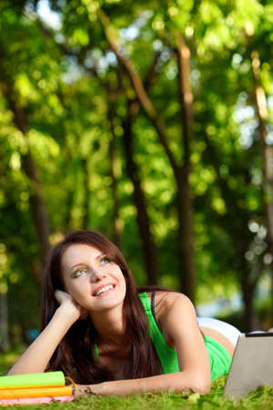 dreaming student woman laying on grass in summer park photo