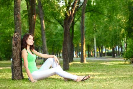 purposeful: brunette woman sitting under the tree at summer park