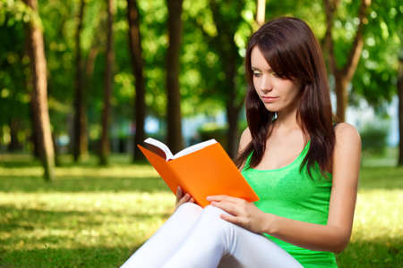 brunette beautiful woman reading book at summer park photo