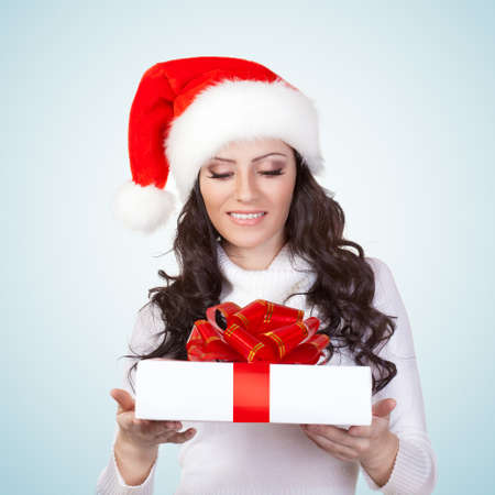 woman wearing christmas hat looking at gift box photo