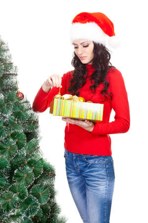 artifical: brunette woman taking toy for artifical fur tree over white Stock Photo