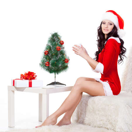 woman wearing santa costume sitting on the sofa and holding mug photo