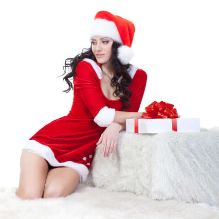 brunette in santa costume sitting on sofa over white photo
