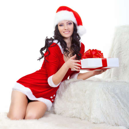 helpers: beautiful woman in santa costume holding gift box over white