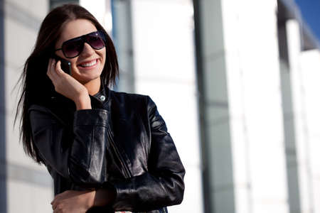 woman wearing leather jacket talking by phone outdoors photo