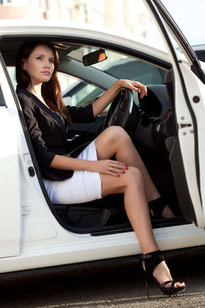 sexy woman sitting in white car photo