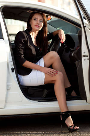 sexy brunette  woman sitting in white car photo