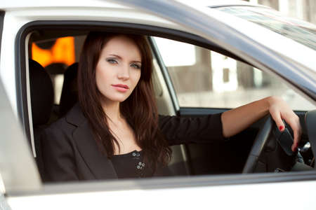 woman sitting in white car, looking trough window photo