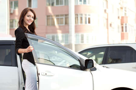 woman in white: brunette woman standing near her white car