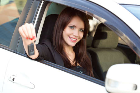 brunette woman in car holding key photo