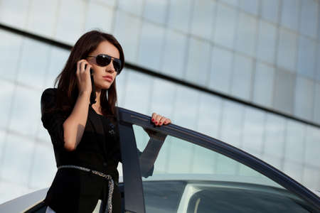 woman standing near car and calling by phone photo