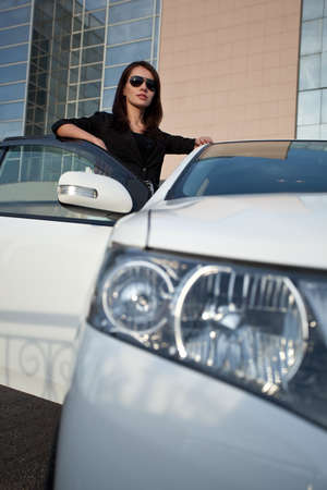 woman in sunglasses standing near car, wide angle photo
