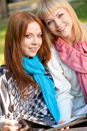 two sisters with photo album sitting in the summer park and looking at camera Stock Photo - 11871907