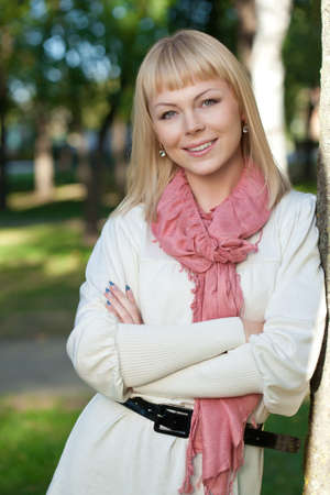 smiling blond woman wearing pink scarf near tree in the summer park photo