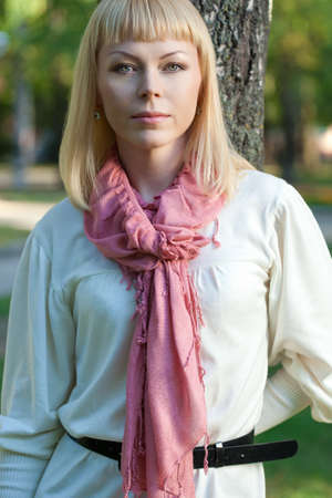 blond woman wearing pink scarf near tree in the summer park photo