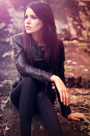 brunette woman sitting on the ground. Specially toned fashion photo photo