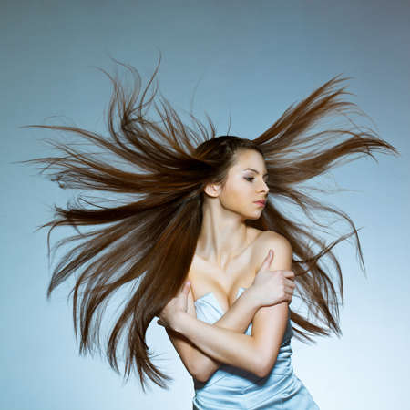 woman with flying hair embracing herself photo