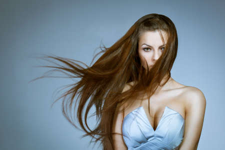 wind dress: beautiful woman with flying to the right hair.  Studio portrait