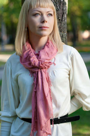 dreaming blond woman wearing pink scarf near tree in the summer park photo