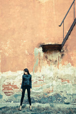 brunette woman wearing leather jacket on ruins near stairway photo