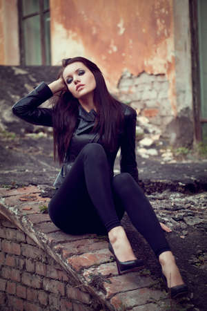 beautiful woman wearing leather jacket sitting on ruins photo