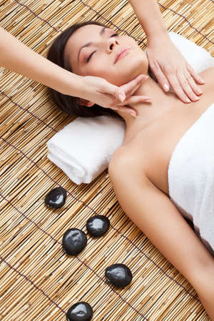 aroma therapy: brunette woman in spa salon. Massage of neck and face