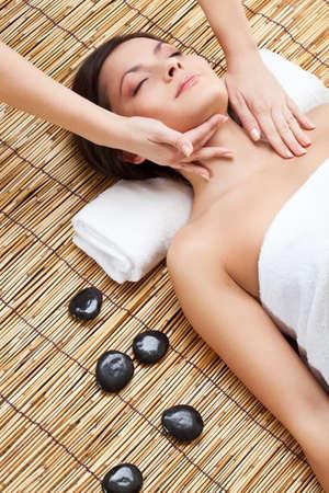 sensual massage: brunette woman in spa salon. Massage of neck and face