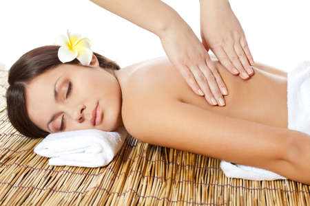 massage table: woman receiving back massage at spa salon Stock Photo