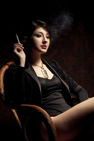 brunette sexy woman sitting in wood chair and smoking photo