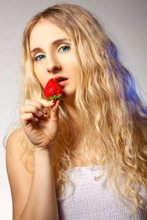 lustful: blonde woman with curly hairs holding red strawberry