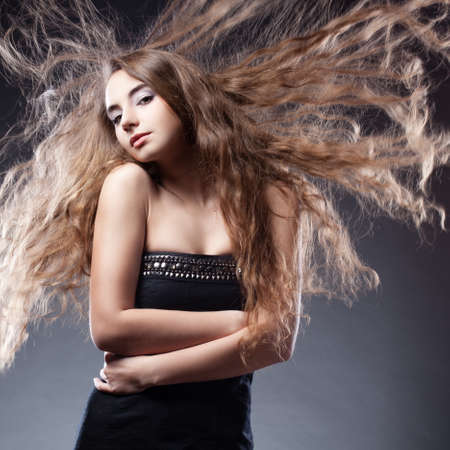 woman with long flying  hair hugging herself photo