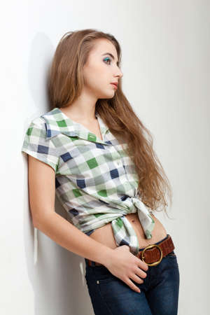young woman wearing  jeans standing near white wall Stock Photo - 13004741