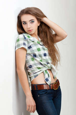 young woman wearing country style clothes, studio portrait near wall Stock Photo - 13004691