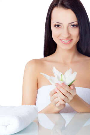 beautiful smiling woman wearing towel holding lily flower photo