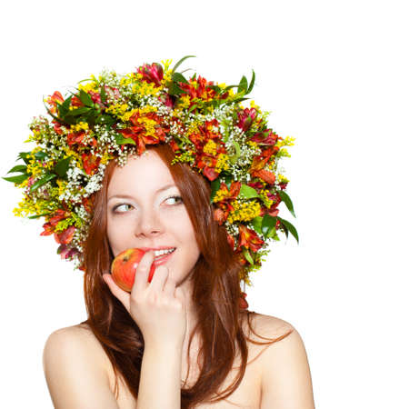 red haired woman: red haired woman with flower wreath on head over white holding apple