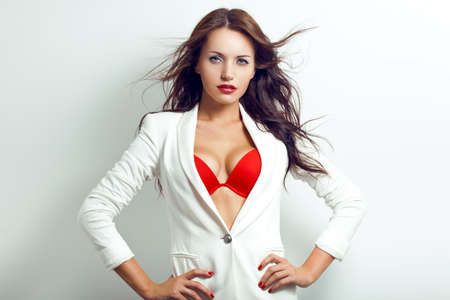 portrait of sexual brunette woman with flying hair wearing red bra and white jacket over white wall 版權商用圖片